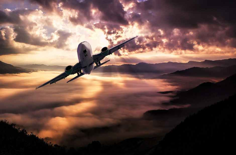 airplane flying under white clouds during night time